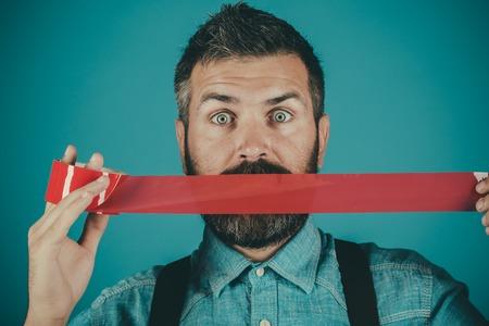 접착 테이프로 입을 감싸는 남자.