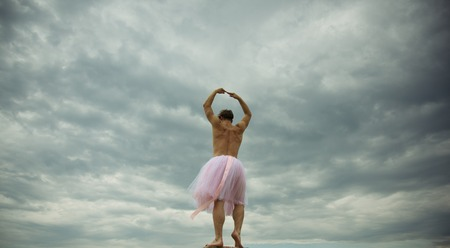 Man dancing in tutu at ballet studio. Funny man freak. Man in ballerina skirt outdoor. Inspiration dreaming. Crazy ballerina. drag queen. Enjoying his favorite music. fun in motion. dancing in sky Stock Photo