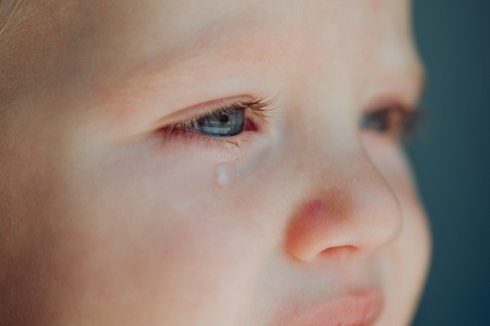 Baby met traan die over zijn wang rolt.