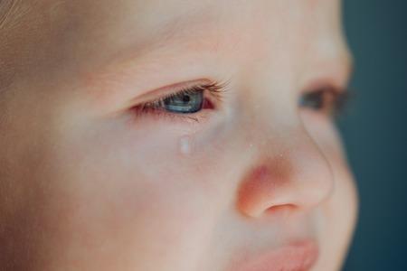 Dziecko ze łzami spływającymi mu po policzku.