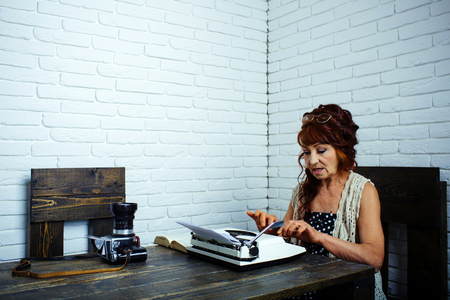 Senior writer at desk. Female reporter or journalist writing on typewriter