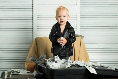 Startup business costs. Boy child with money case. Little entrepreneur work in office. Little boy count money in cash. Small child do business accounting in startup company. Money circulation