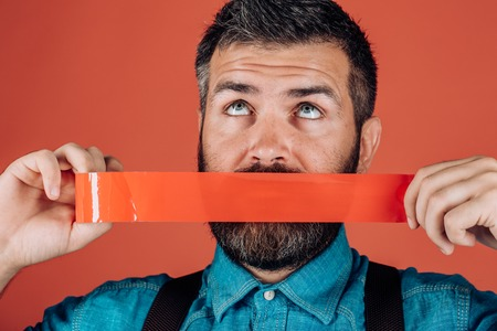 Concept freedom of speech and press. International Human Right day. censorship. Brutal bearded male. Mind control and propaganda. man wrapping mouth by adhesive tape. False advertising concept