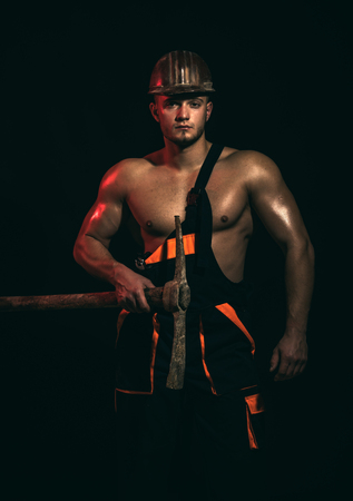 Caution, under construction. Muscular man worker. Man miner with mining equipment.