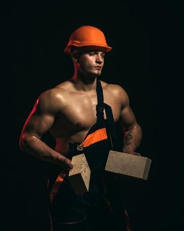 Bauarbeiter oder Baumeister bei der Arbeit auf der Baustelle. Mann Arbeiter halten Ziegelsteine in muskulösen Händen. Muskulöser Mann macht Maurerarbeiten