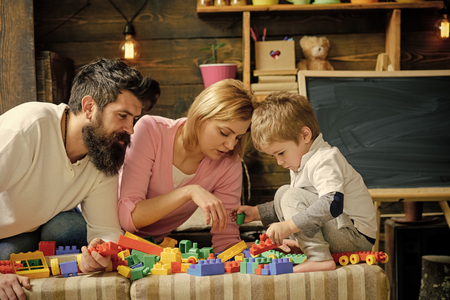 Father, mother and cute son play with constructor bricks. Kid with parents play with plastic blocks, build construction. Family on busy face spend time together in playroom. Caring parents concept