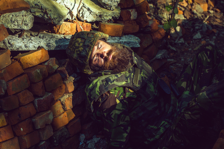 Killed soldier with beard on face in camouflage and military helmet on stone brick background.