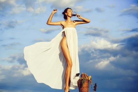 Chica guapa con botella de vino sobre el cielo Foto de archivo