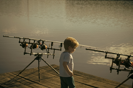 Little boy with fishing rods on pier