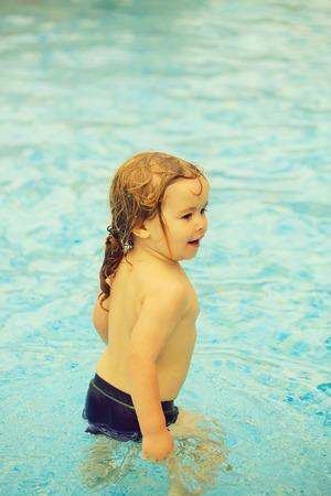 Cute cheerful baby boy has bath in outdoor pool