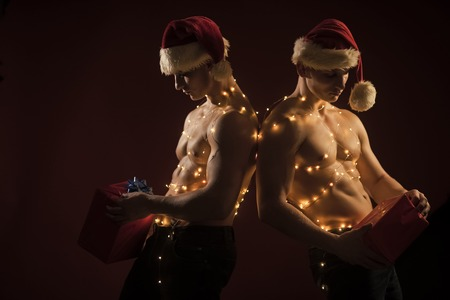 Young men in santa costume, present for girls. Imagens