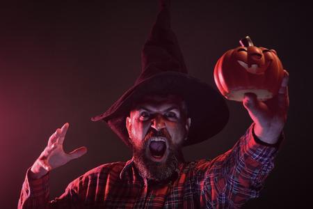 Halloween hipster in wizard hat holding pumpkin
