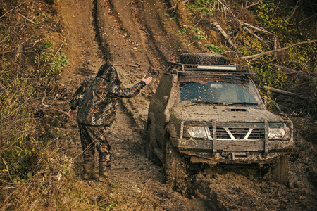 Man in camouflage clothing stands near suv covered with dirt 写真素材