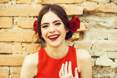 fashionable happy woman in red dress with rose in hair
