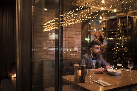Date meeting of hipster awaiting in pub. Waiting for date of bearded man with wine glass Stock Photo
