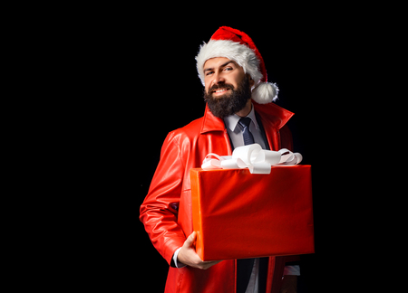Santa claus with red Christmas gift box. Bearded modern santa on black background wishes Merry christmas and Happy new year. Santa on black backgroud isolated. Stock Photo