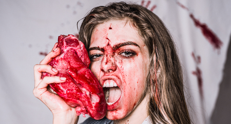 Steak concept. Hungry woman with meat steak. Hungry emotional angry woman screaming. A sensual bloody woman want eat. Hungry and angry faces. Crazy horror story. Sexy kitchen and juicy steak.