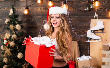 Merry Christmas and Happy Holidays. Big present gift on xmas morning. Happy woman with red new year present gift. Celebrate and decorate the house. Christmas wishes come true if you believe.