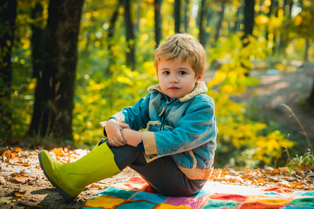 Autumn dream. Cute children with Autumn Leaves on Fall Nature Background. Children sits in the forest and dreams. Comfortable child clothes concept. Childhood dream.