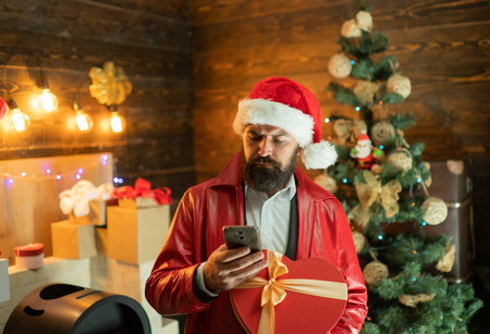 Santa hold mobil and wishes Merry christmas and Happy new year. Santa claus with red Christmas gift box. Stock Photo