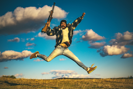 Hunter with shotgun gun on hunt. Crazy hunter on sky background.