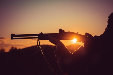 Calibers of hunting rifles. Rifle Hunter Silhouetted in Beautiful Sunset. Silhouette of the hunter. Pulled the trigger of the shotgun. Barrel of a gun.