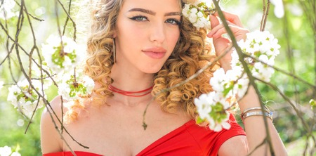 Summer girl and sensual moment. Beauty woman outdoors in blooming trees. Beauty model in flowers. Spring girl in blooming garden. Stock Photo