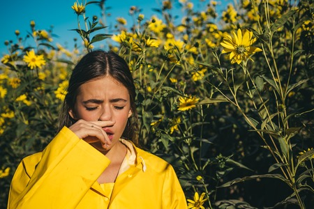 The girl suffers from pollen allergy during flowering and uses napkins. Young woman got nose allergy, flu sneezing nose. Woman is blowing her nose near flowers in bloom. Allergy. Stock fotó