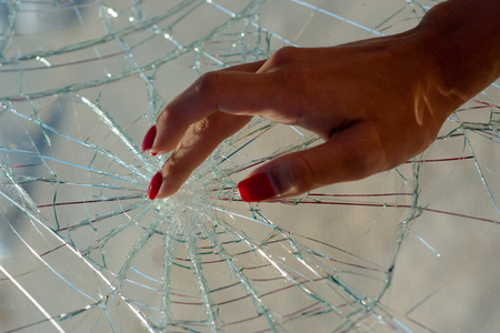 Sensual touch. Nail care and nail protection. Red manicure. Broken glass