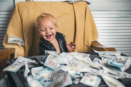Bonne affaire. Un petit enfant fait de la comptabilité d'entreprise dans une entreprise en démarrage. Un petit entrepreneur travaille au bureau. Enfant garçon avec cas d'argent. Petit garçon compte de l'argent en espèces. Frais de démarrage d'entreprise Banque d'images