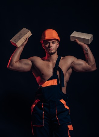 Building up great things. Construction worker or builder at work at building site. Bricklayer worker. Man worker hold bricks in muscular hands. Muscular man does masonry work