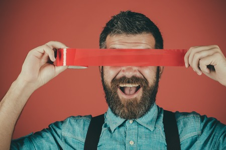 censorship. Brutal bearded male. Civil rights. Concept freedom of speech and press. International Human Right day. Mind control and propaganda. man wrapping mouth by adhesive tape. mass Reklamní fotografie