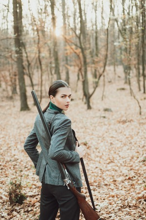 Hunter woman hunting. Hunting in autumn forest. Portrait of beauty woman Hunter. Hunting season.