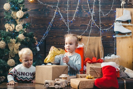 Child new year. kids christmas. Children playing with gift. New Years Eve. Christmas gift box and happy family. Kids opening Xmas presents. Winter evening at home. Happy smiling child with christmas gift box. Stok Fotoğraf