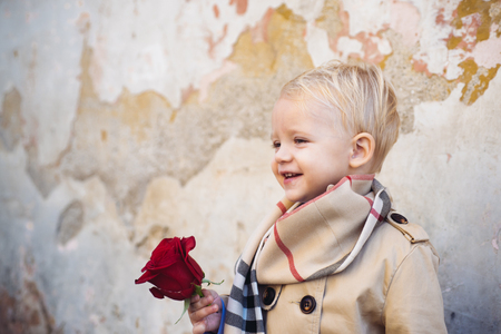 First date. Little boy in love with rose. Child wait, loneliness concept. First love. Valentines day background. Friendly romantic boys in old town background. Autumn fashion kids. Stock Photo