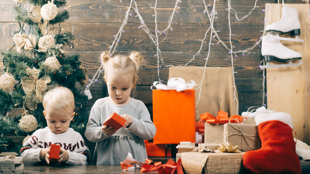 Kids opening Xmas presents. Winter evening at home. Happy smiling child with christmas gift box. Stok Fotoğraf