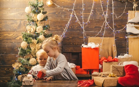 Christmas gift box and happy family. Kids opening Xmas presents. Winter evening at home. Happy smiling child with christmas gift box.