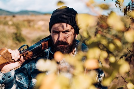 Bearded hunter man holding gun and walking in forest. Hunter with shotgun gun on hunt. Close up Portrait of hamdsome Hunter.