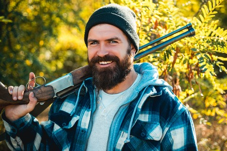 Pictures for Barbershop. Bearded hunter man holding gun and smile. Hunter with long beard on hunt. Barbershop vintage. Ideas about Barber shop and Barber salon. Stock Photo