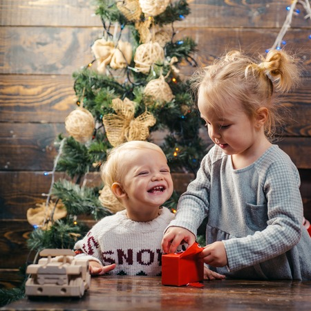 Children playing with gift. Christmas gift box and happy family. Kids opening Xmas presents. Winter evening at home. Happy smiling child with christmas gift box.