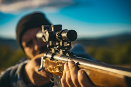 Close up snipers carbine at the outdoor hunting. Hunter aiming rifle in forest. Hunter with shotgun gun on hunt. Hunter with Powerful Rifle with Scope Spotting Animals.