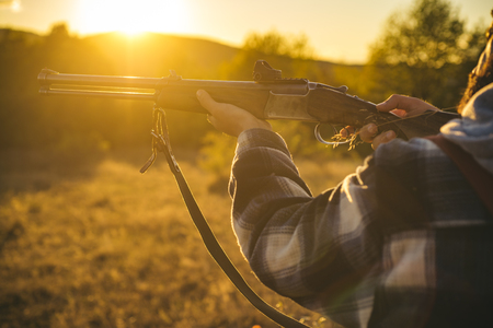 Hunter with shotgun gun on hunt. Illegal Hunting Poacher in the Forest. American hunting rifles. Hunting without borders. Stock Photo