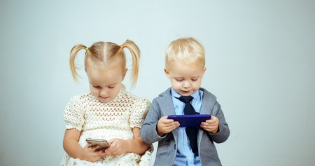 Kids mobile addicted. Little couple with phone. Boy and girl shy on date online. Love, friendship concept. Valentines day. Social concept. Stock Photo