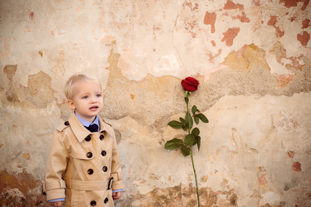 Little boy in love with rose. First love. Valentines day background. Friendly romantic boys in old town background. Autumn fashion kids. First date. Stok Fotoğraf