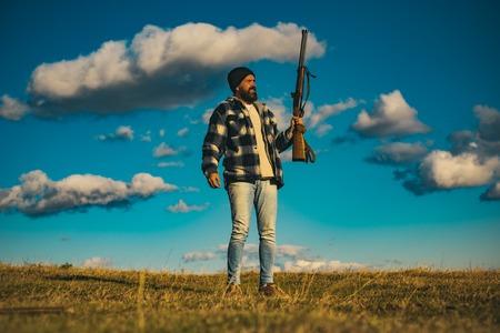 Bearded hunter man holding gun and walking in forest. Hunter with shotgun gun on hunt.