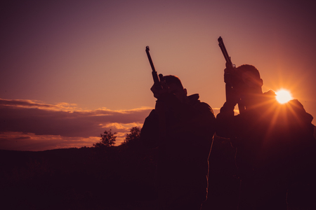 Silhouette of the hunter. Hunting Equipment for sale. Rifle Hunter Silhouetted in Beautiful Sunset. Copy space for text.
