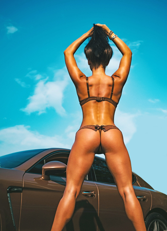 Luxury woman. Sport car and luxurious butt woman. Luxury lingerie. Sexy ass near golden brown sports car on luxury background. Pinup bikini. Imagens