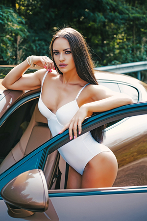 Luxury woman. Sport car and luxurious butt woman. Sexy ass near golden brown sports car on luxury background.