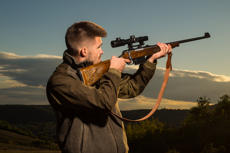 Hunting Gear - Hunting Supplies and Equipment. Hunter with shotgun gun on hunt. Hunter with Powerful Rifle with Scope Spotting Animals.