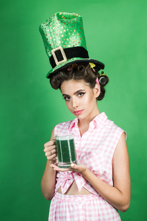 St. Patricks Day pretty girl in vintage style. pinup girl with fashion hair. pin up woman with trendy makeup. retro woman drink summer cocktail. green. lepricon Stock Photo